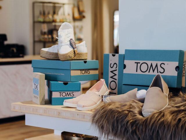 Verschillende paren TOMS schoenen en schoenendozen
